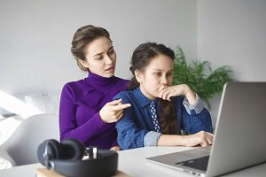 Serious teenage girl doing homework, making research, looking for information online on internet using laptop pc while mother helping her, sitting behind and helping her, pointing finger at screen