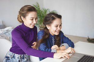 People, relationships, technology, fun and leisure concept. Two cheerful sisters playing video games using laptop at home. Happy mother and daughter having fun, enjoying online communication