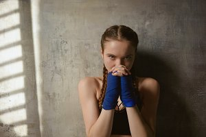 Martial arts, fighting, boxing and kickboxing. Close up portrait of self determined confident sporty girl clasping hands wrapped in bandages, ready for fight, staring at camera with focused look
