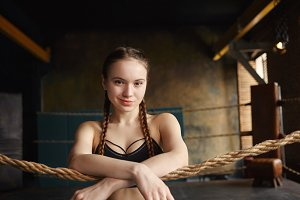 Confident teenage girl with two braids standing in boxing ring, waiting for her instructor or coach, smiling at camera, crossing arms on rope in front of her. Fitness, sports and martial arts