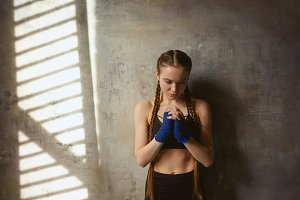 Isolated shot of beautiful serious young European woman professional kickboxer with two braids wearing handwraps and stylish sports outfit, clasping hands on her chest while praying before fight