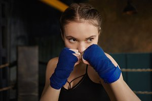 Sports, fighting, training and physical exercise concept. Indoor shot of concentrated young Caucasian woman wearing top and handwraps clenching fists in front of her face, ready to deliver punch
