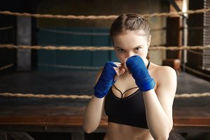Sports, determination, fitness and martial arts. Sporty girl wearing black dry fit top and boxing bandages standing in defensive posture, fighting against invisible enemy, boxing ring in background