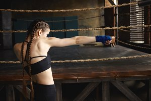 Sideways shot of determined serious young female with strong muscular arms and two braids punching air in front of her as if boxing against invisible opponent. Sports and martial arts concept