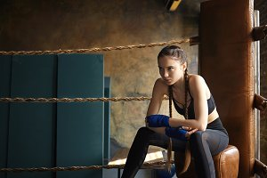 Serious pretty girl with two braids setting her mind on fight, sitting in the content of boxing ring, staring ahead of her with focused determined look. Martial arts, kickboxing and fighting