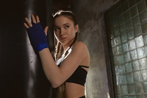 Cute girl attending self defense classes, posing at punching bag, wearing sports bra and boxing bandages. Picture of serious young female fighter exercising in gym, looking tired and exhausted
