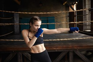 Fit young female boxer with perfect muscular body mastering punching techniques in gym, focused on process, reaching out hand and looking ahead of her, having serious concentrated facial expression