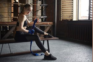 People, sports, fitness, activity and health concept. Active athletic young European female wearing black sneakers and sports clothes, wrapping boxing bandages, getting ready before training