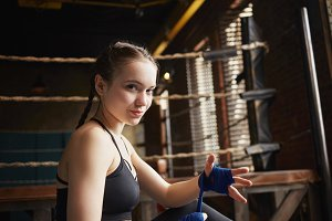 Sporty girl with braids sitting indoors, wrapping bandages on her hands, preparing for fight. Beautiful young sportswoman in black top smiling at camera, tying hand wraps before boxing training in gym