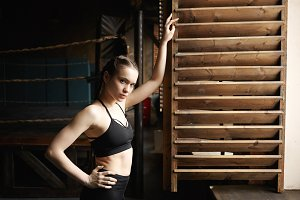 Sports, fitness, style and fashion concept. Confident attractive young sportswoman with muscular arms posing at window, leaning on wooden shutter, looking at camera, keeping hand on her waist