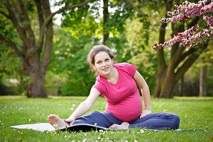 Pregnant woman exercising in the spring park