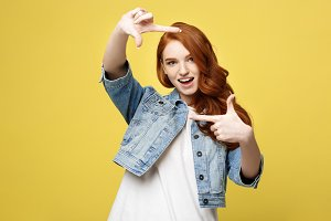 Portrait of young beautiful ginger woman with freckles cheerfuly smiling making a camera frame with fingers. Isolated on yellow background. Copy space.