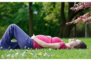 Pregnant woman relaxing in the spring park
