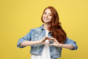 Lifestyle Concept: Beautiful attractive woman in denim making a heart symbol with her hands