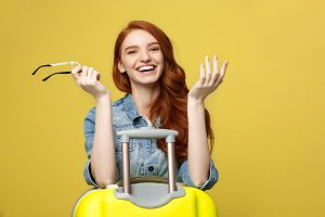 Travel Concept: Happy tourist woman wearing jean clothes ready for travel with suitcase and passport. Isolated over bright yellow background.