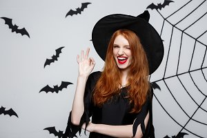 Halloween witch concept - happy halloween ginger hair witch holding ok sign with fingers posing over grey background.