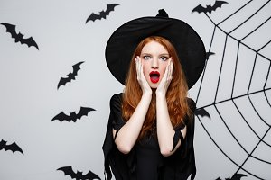 Halloween Concept - Beautiful caucasian witch shocking with something over grey background.