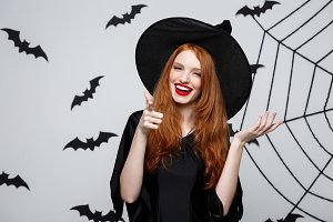 Halloween witch concept - Happy Halloween Witch pointing finger on side over dark grey studio background with bat and spider web.
