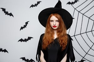 Halloween Concept - Beautiful serious witch with angry facial expression over grey background.
