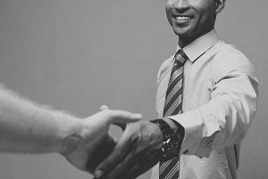 Business concept - Close-up of two confident business people shaking hands during a meeting.Black and white