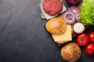 Hamburger Building Kit. Fresh ingredients for Burger on dark stone table. Top view with copy space