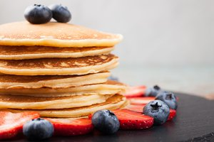Delicious pancakes close up, with fresh blueberries, strawberries on a light background