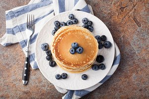 Delicious pancakes close up, with fresh blueberries on rusty background. Top view