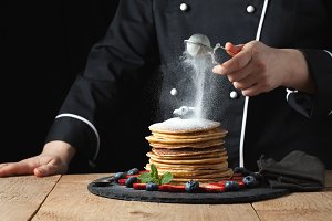 Serving pancakes with powdered sugar and berries. Chef woman hand. Beautiful food still life. slightly toned image, dark black background with text area. Horizontal view