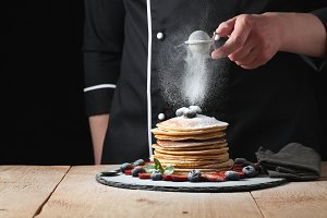 Serving pancakes with powdered sugar and berries. Chef man hand. Beautiful food still life. slightly toned image, dark black background with text area. Horizontal view