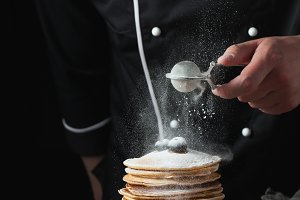 Serving pancakes with powdered sugar and berries. Chef man hand. Beautiful food still life. slightly toned image, dark black background