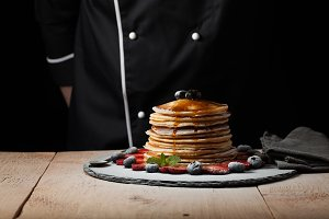 Front view of Stack of homemade plain pancakes with strawberries, blueberries and maple syrup served on black plate on black background with selective focus. With copy space
