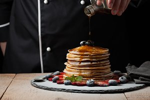 The chef pours maple syrup on pancake stack with blueberries and strawberries on black background