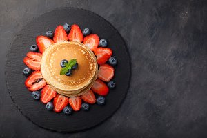 Delicious pancakes close up, with fresh blueberries, strawberries on a black stone background. Top view with copy space