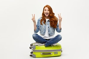 Travel concept: young smiling caucasian woman siting on suitcase showing two fingers. Isolated over white background.