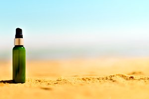 Bottle of sunscreen in sand against sea background with copyspace. Vacation and travel wallpaper. Skin care concept. Banner
