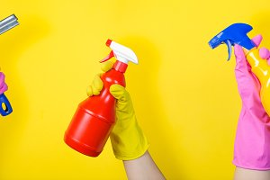 Cleaning concept - hands holding supplies on bright background