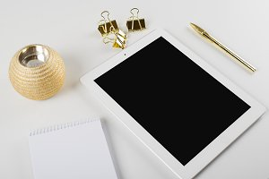 Tablet and notebook next to ballpoint pen and golden clips on white background.