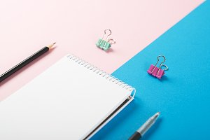 Note book next to pencil, ballpoint pen and colorful clips on pink and blue background. Mockup.