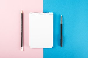 Notebook next to pencil and black pen on pink and blue background. Mockup. Stationery...