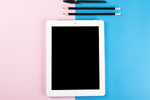 Tablet next to pencils and pen on pink and blue background.