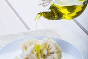Pouring extra virgin olive oil over a boiled cauliflower