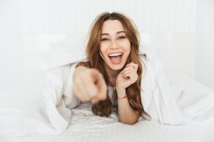 Portrait of an excited young woman lying in bed