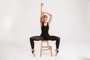 Amazing young woman ballerina sitting