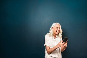 Happy mature old woman using mobile phone.