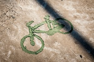 bicycle sign on concrete with green