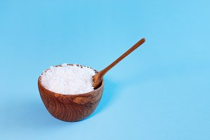 coconut flakes in wooden bowl with spoon, isolated