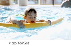 Little boy swimming in the pool with