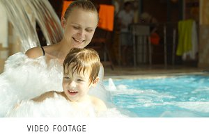 Mother holding son splashing