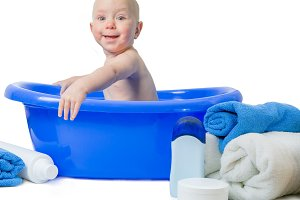 Baby in ble bath with towel and bottles