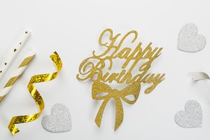 Birthday concept - silver and gold decorations on white background